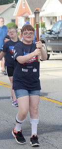 Riley Baxter carries the torch during the 16th leg of the Special Olympic's Law Enforcement Torch Run that started Wednesday morning in downtown Effingham. The event raises awareness and money for the Special Olympics. The state competitions begin on Friday. Graham Milldrum photo