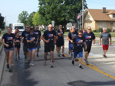 Law enforcement officers join Special Olympian Bradlee Todd, who is carrying the torch, during the start of the the 16th leg of the Special Olympic's Law Enforcement Torch Run started Wednesday morning in downtown Effingham. The event raises awareness and money for the Special Olympics. The state competitions begin on Friday. Graham Milldrum photo