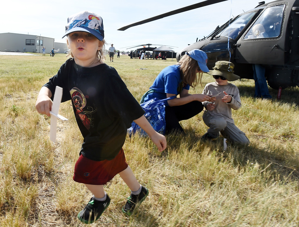 """. Alex Samet-Bjornsen, 3, \""""flies\"""" his balsa wood plane around a blackhawk helicopter during the 2018 Longmont Airport Expo at Vance Brand Airport on Saturday. For more photos, go to dailycamera.com. Cliff Grassmick  Staff Photographer  June 23, 2018"""