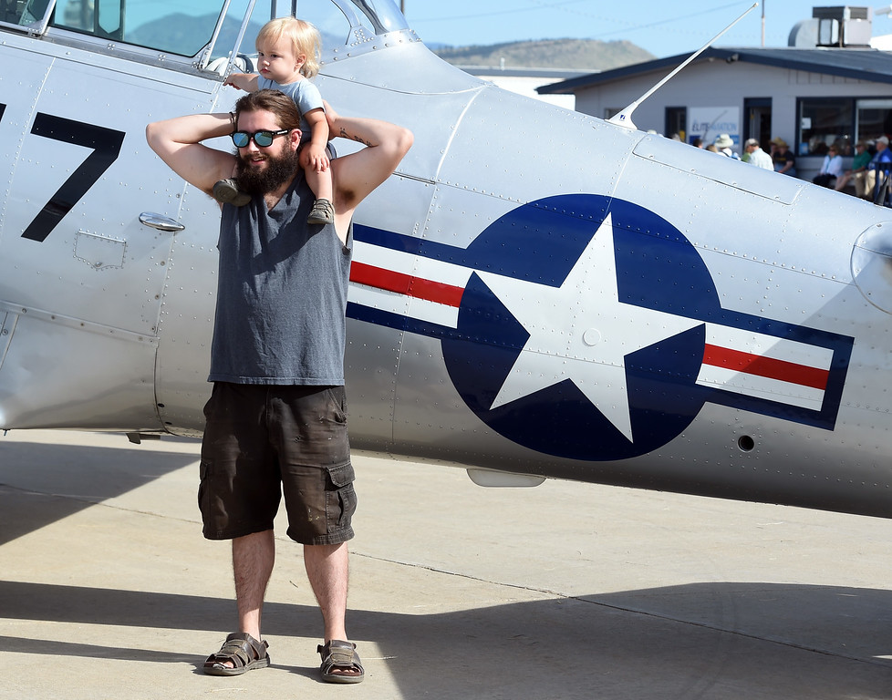. Jesse Holt is photographed with his son, James, 18-months, with one of the vintage aircraft during the 2018 Longmont Airport Expo at Vance Brand Airport on Saturday. For more photos, go to dailycamera.com. Cliff Grassmick  Staff Photographer  June 23, 2018