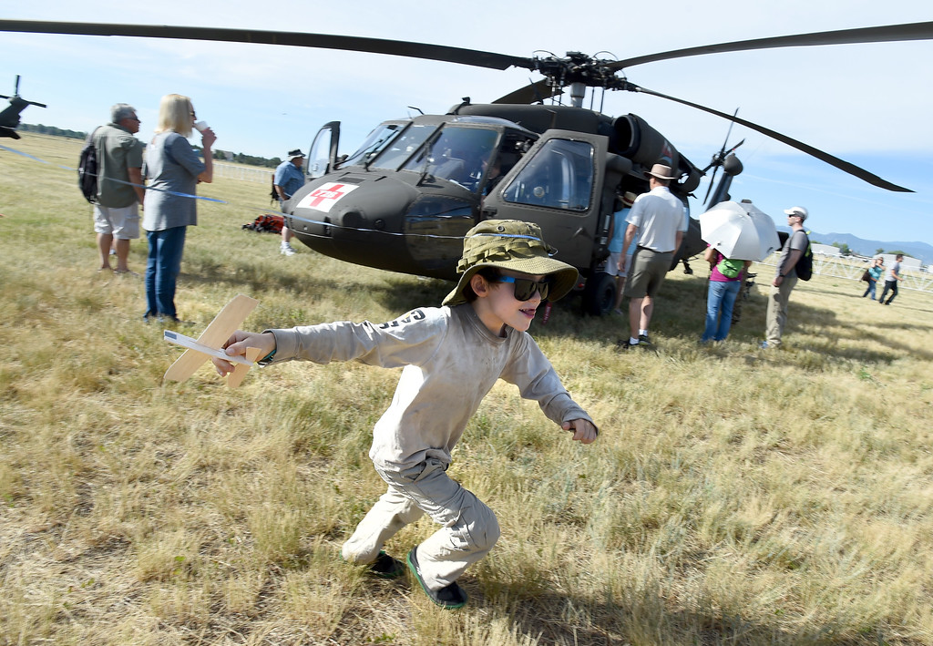 """. Ivan Samet-Bjornsen, 6, \""""flies\"""" his balsa wood plane around a blackhawk helicopter during the 2018 Longmont Airport Expo at Vance Brand Airport on Saturday. For more photos, go to dailycamera.com. Cliff Grassmick  Staff Photographer  June 23, 2018"""