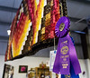 A quilt with its best of show ribbon hangs in the Ray Voshall Exhibition Building.
