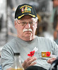 Vietnam Veteran Ted Mazurowski unfolds poppies to be placed into a stand.