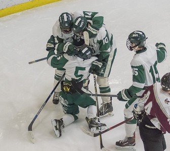 Owen Coates (#5) is surrounded by his teammates after his goal
