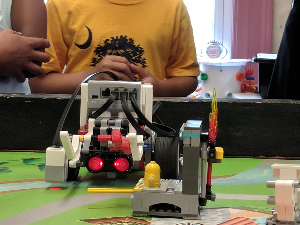. Leah McDonald - Oneida Daily Dispatch Team Super Bot\'s Lego robot pushes a lever to put out a fire during the Oneida Public Library\'s Lego robotics summer camp on Friday, Aug. 24, 2018.