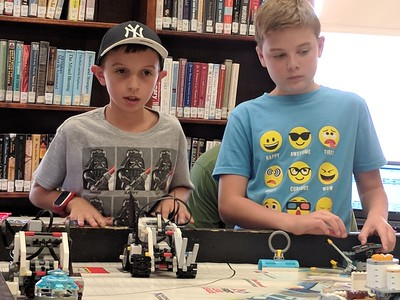 Leah McDonald - Oneida Daily Dispatch Jacob Higgins, 10, left, takes a practice run with his robot while Sullivan Tifft, 11, watches at the Oneida Public Library on Friday, Aug. 24, 2018.