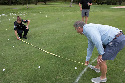 shumskis04-Woodstock_officer_Jessica_Ryan-LeBlanc_and_Zacks_Place_founder_Norm_Frates_measuring_the_distance_of_one_ball