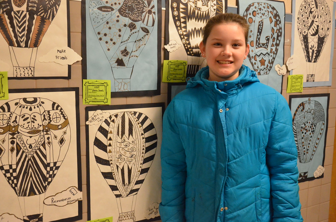 Leah McDonald - Oneida Daily Dispatch Victoria Leahey, 11, poses in front of her art work at the Oneida City School District's district-wide art show at Otto Shortell Middle School on Tuesday, March 20, 2018. The show runs until April.