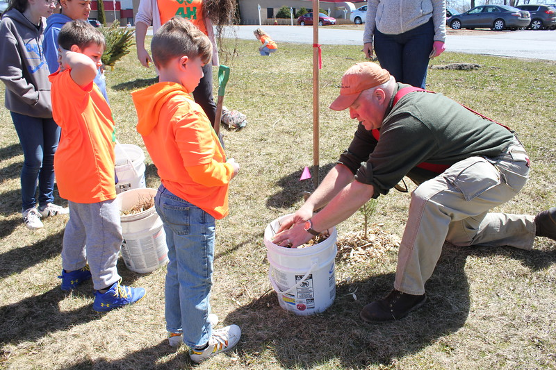 Charles Pritchard - Oneida Daily Dispatch Oneida Rotary Perry Tooker IV explains the importance of mulching for the new saplings for Earth Day on Sunday, April 22, 2018.