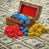 Chuck Knowles - Old wooden box filled with game dice on a sheet of money