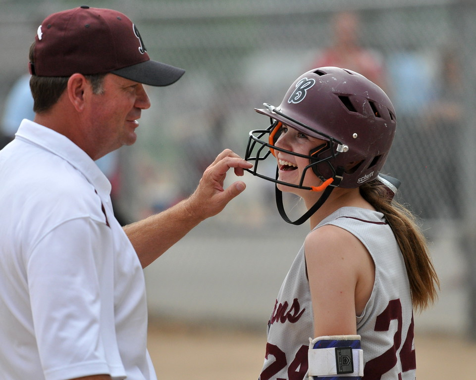 . Berthoud coach Buddy Kouns, left, shares a laugh with sophomore Jordan Schachterle after she took a foul ball to the helmet in the on-deck circle during the Berthoud Spartan Classic on Saturday Sept. 9, 2017 at the Barnes Complex. (Cris Tiller / Loveland Reporter-Herald)