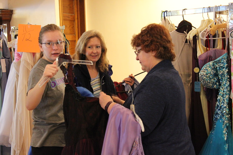 Charles Pritchard - Oneida Daily Dispatch Alannah Henry, 17, and her mother Julie Titus of Oneida, middle, look through a number of dresses at the First Presbyterian Church's Prom Dress Giveaway with volunteer Becky Ewen on Saturday, Feb. 10, 2018.