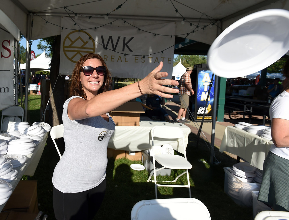 . Sheree Nuss, of WK Real Estate, tosses out a flying disc to passers by during the annual Rhythm on the River in Longmont on Saturday. For more photos,  go to dailycamera.com.  Cliff Grassmick / Staff Photographer/ July 14, 2018