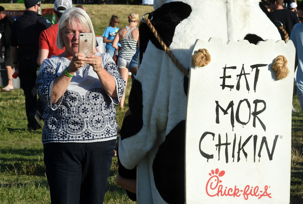 . Brenda Davis takes a photo of her grandson, Mason Davis, with the Chick-fil-A cow during the annual Rhythm on the River in Longmont on Saturday. For more photos,  go to dailycamera.com.  Cliff Grassmick / Staff Photographer/ July 14, 2018