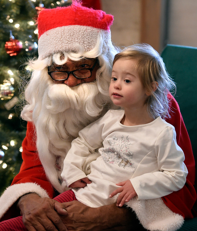. BOULDER, CO - November 29, 2018: Uma Omafray, 3, was able to meet Santa, Rich Lopez, on her birthday. Santa\'s House, the annual benefit for families and children of Boulder, is open to the public Saturday and Sunday, December 1 & 2 from 10 AM to 4 PM.  Santa\'s House, which is sponsored by the Boulder Area Alumnae Panhellenic, is  at 890 11th Street, Boulder, the Pi Beta Phi sorority house.  Admission is $5 per person and each child receives a personalized keepsake ornament.  (Photo by Cliff Grassmick/Staff Photographer)