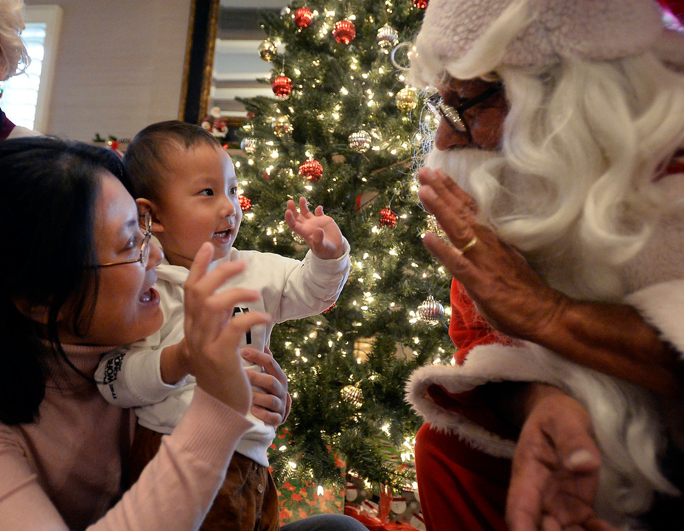 . BOULDER, CO - November 29, 2018: Yan Li and her son, Eddie, 2, were  able to meet Santa, Rich Lopez,  at Santa\'s House.  was able to meet Santa, Rich Lopez, and Mrs Santa, Jeannie DeMarinis. Santa\'s House, the annual benefit for families and children of Boulder, is open to the public Saturday and Sunday, December 1 & 2 from 10 AM to 4 PM.  Santa\'s House, which is sponsored by the Boulder Area Alumnae Panhellenic, is  at 890 11th Street, Boulder, the Pi Beta Phi sorority house.  Admission is $5 per person and each child receives a personalized keepsake ornament.  (Photo by Cliff Grassmick/Staff Photographer)
