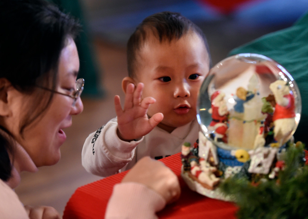 . BOULDER, CO - November 29, 2018:  Yan Li and her son, Eddie, 2, were amazed by the snow globe at Santa\'s House.  Santa\'s House, the annual benefit for families and children of Boulder, is open to the public Saturday and Sunday, December 1 & 2 from 10 AM to 4 PM.  Santa\'s House, which is sponsored by the Boulder Area Alumnae Panhellenic, is  at 890 11th Street, Boulder, the Pi Beta Phi sorority house.  Admission is $5 per person and each child receives a personalized keepsake ornament.  (Photo by Cliff Grassmick/Staff Photographer)