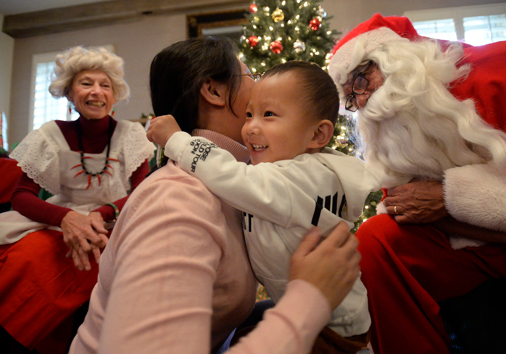 . BOULDER, CO - November 29, 2018:  Yan Li and her son, Eddie, 2, were able to meet Santa, Rich Lopez, and Mrs Santa, Jeannie DeMarinis. Santa\'s House, the annual benefit for families and children of Boulder, is open to the public Saturday and Sunday, December 1 & 2 from 10 AM to 4 PM.  Santa\'s House, which is sponsored by the Boulder Area Alumnae Panhellenic, is  at 890 11th Street, Boulder, the Pi Beta Phi sorority house.  Admission is $5 per person and each child receives a personalized keepsake ornament.  (Photo by Cliff Grassmick/Staff Photographer)