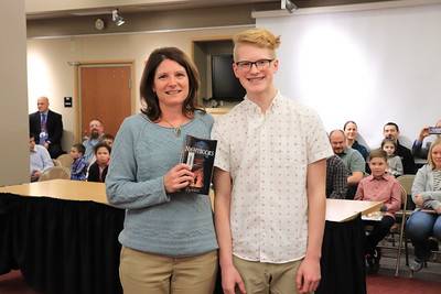 """Brette Confair is presented with """"Nightbooks"""" by Jackson Fink from Williamsport Area Middle School."""
