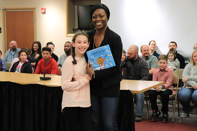 """Barbara Reeves is presented with """"The Word Collector"""" by Ava Fischer from Jackson Primary School."""