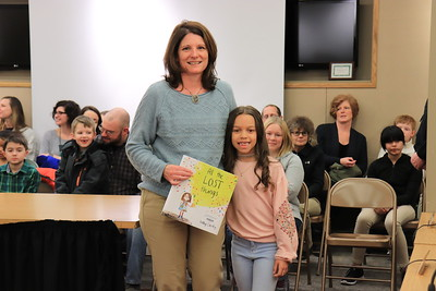 """Brette Confair is presented with """"All Things Lost"""" by Amaya Gainer from Stevens Primary School."""
