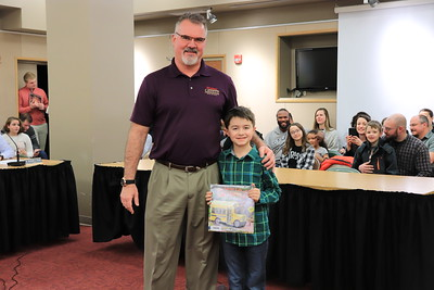 """Marc Schefsky is presented with """"The Secret Life of Squirrels: Back to School"""" by Corbin Kirk from Cochran Primary School."""