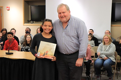 """Patrick Dixon is presented with """"Coming Home"""" by Julisa Martin from Cochran Primary School."""