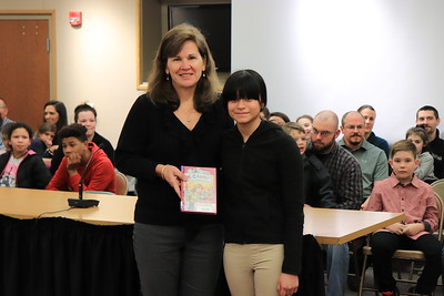 """Vice President Dr. Jane Penman is presented with """"Curious McCarthy's Power of Observation"""" by Faith Nonemaker from Andrew G. Curtin Intermediate."""
