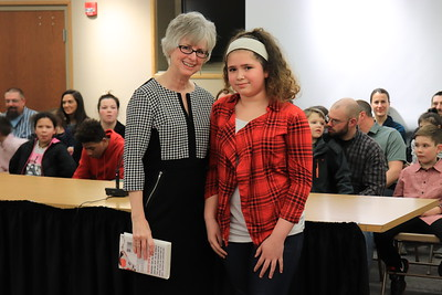 """Dr. Nancy Story Somers is presented with """"The Running Dream"""" by Hailey Copson from Andrew G. Curtin Intermediate."""