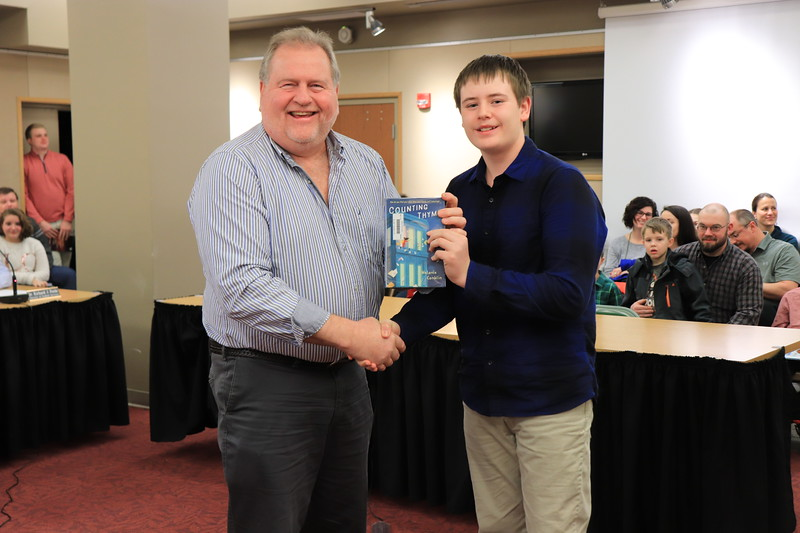"Patrick Dixon is presented with ""Counting Thyme"" by Chais Shief from Williamsport Area Middle School."