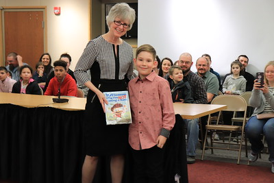 """Dr. Nancy Story Somers is presented with """"101 Reasons Why I'm Not Taking a Bath"""" by Chase Hill from Stevens Primary School."""