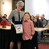 "Dr. Nancy Story Somers is presented with ""101 Reasons Why I'm Not Taking a Bath"" by Chase Hill from Stevens Primary School."