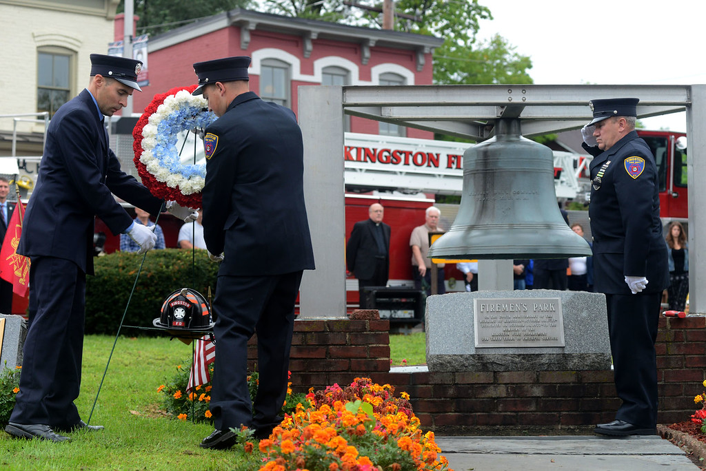 . Tania Barricklo-Daily Freeman                      Jae Verner, left, and Eric Nägeli, both firefighters for the Kingston Fire Department, lay a wreath during the annual September 11  memorial service at Firemen\'s Park Tuesday morning on Washington Ave. in Uptown Kingston. To the right is fire fighter Mike Fitzgerald of Kingston Company 2 who performed the bell ringing of four rounds of five, a tradfition done when a firefighter dies in the line of duty.According to Kingston Fire Chief Mark Brown, on the day of the terrorist attacks, 343 firefighters perished. Since then, the number has risen to 523, with firefighters dying from September 11 related illnesses, such as cancers or pulminary-related illnesses.