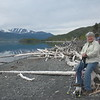 Linda Swarner perched on some of the massive driftwood on shore.