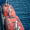 orange life boats attached to cruise ship deck