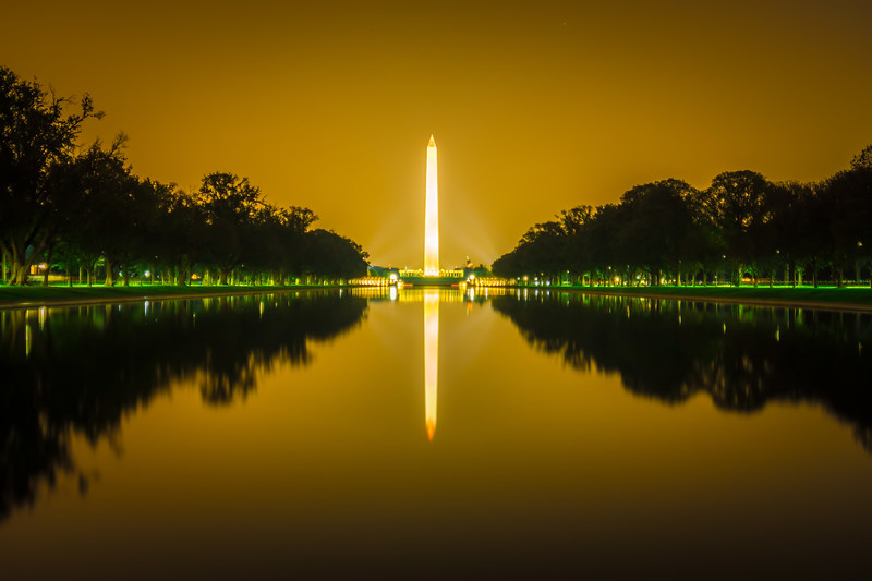 washington memorial tower reflecting in reflective pool at sunset