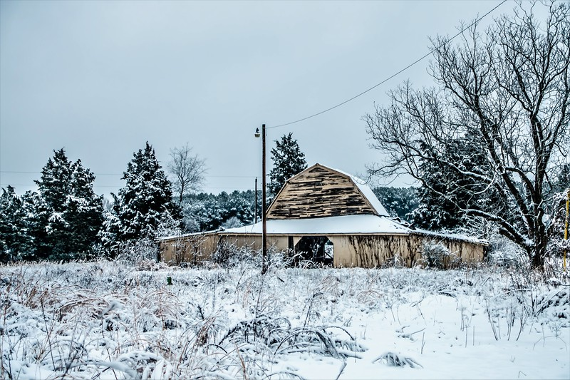 old vintage historic barn on farm covered in snow