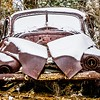 old vintage plymouth automobile in the woods covered in snow