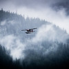 Single Prop Airplane Pontoon Plane flying through fog over Alaska Last Frontier