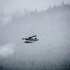 Single Prop Airplane Pontoon Plane flying through fog over Alaska Last Frontier