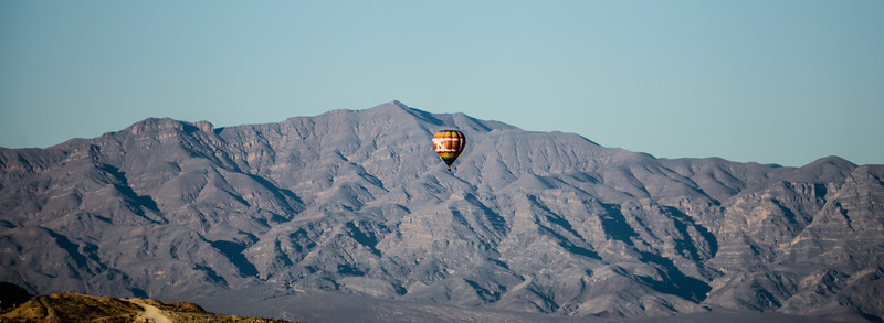 hot air balloon flying above red rock canyon