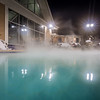 hot tubs and ingound heated pool at a mountain village in winter at night