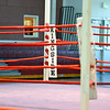 Empty boxing ring with red ropes for match