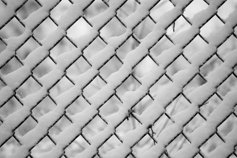 snow stuck on chainlink fence enclosure after snow fall