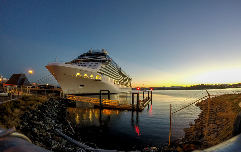 cruise ship moored in port of a city at sunset