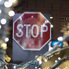 stop sign and holiday christmas lights in a city at intersection