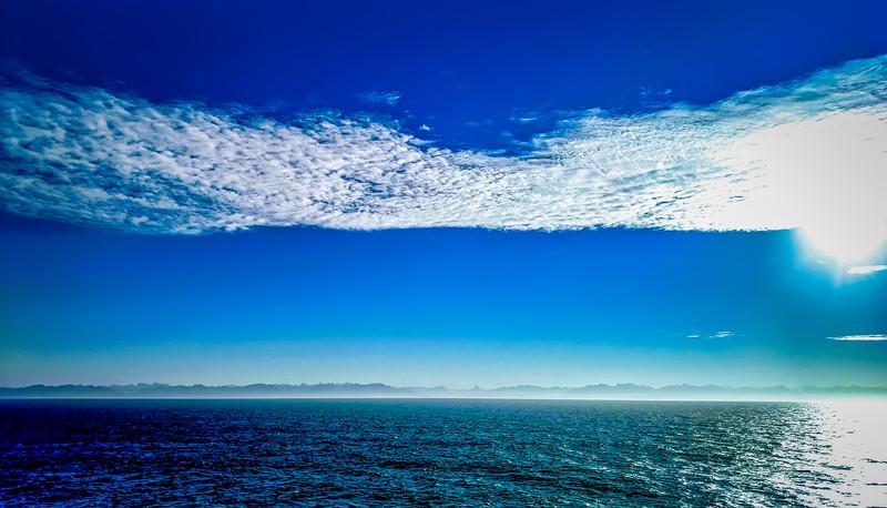 Seascape and mountain landscape on blue sky background in alaska