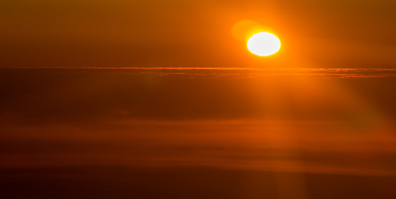 sunset or sunrise from an airplane peeking through the clouds