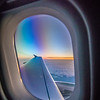Clouds and sky as seen through window of an aircraft at sunrise