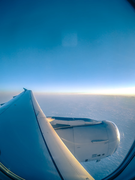 looking out airplane window and flying above the clouds